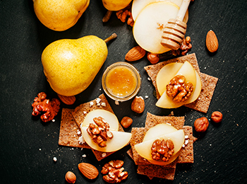 Appetizer canape with pear, honey, hazelnuts, almonds and cottag