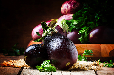 Fresh aubergines on vintage wooden background, selective focus