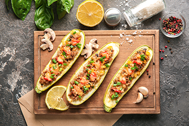 Board with meat stuffed zucchini boats and spices on grunge table