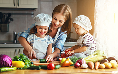Healthy eating. Happy family mother and children prepares  vegetable salad